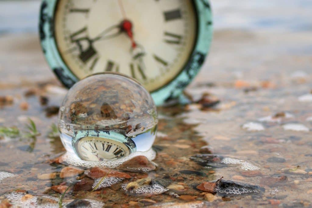 Transparent glass ball reflecting an antique alarm clock on a wet sandy beach