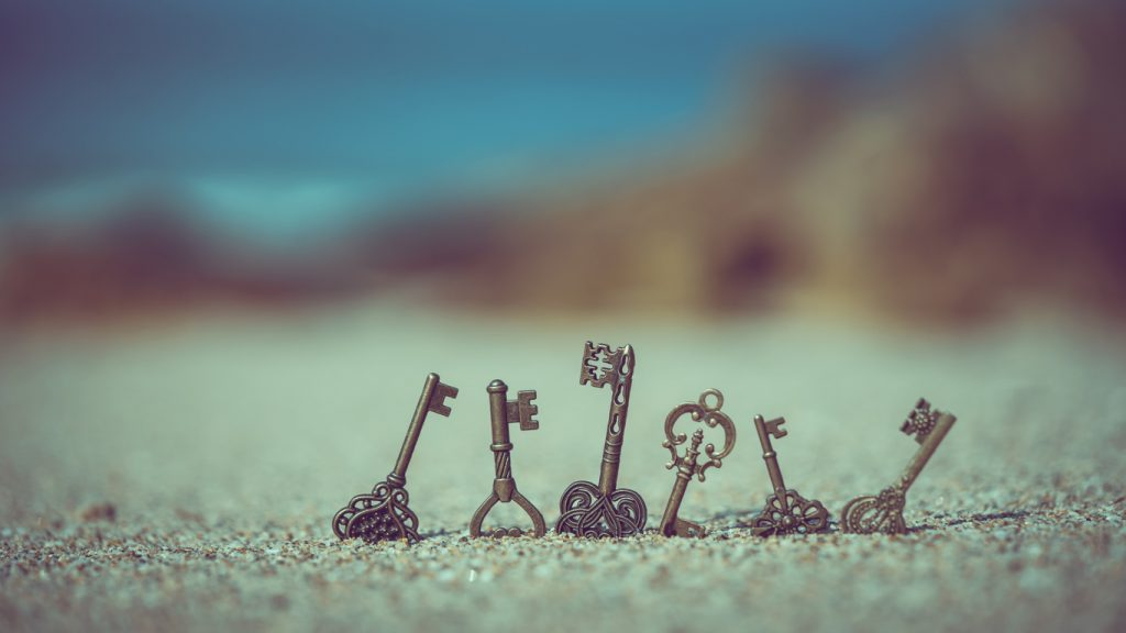 Vintage keys sticking out of the sand on a beach