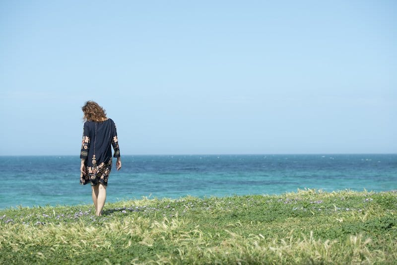 Midlife woman walks in a meadow by the sea in Pane e Pomodoro's beach in Bari (Apulia)