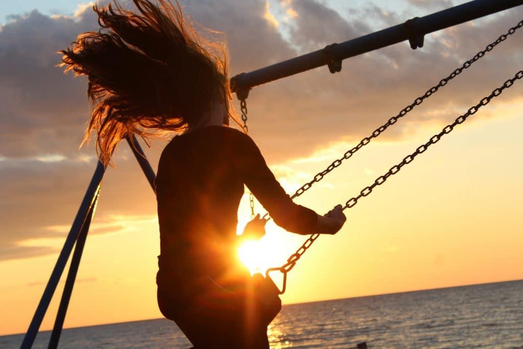 Women on a swing in front of ocean, having fun.